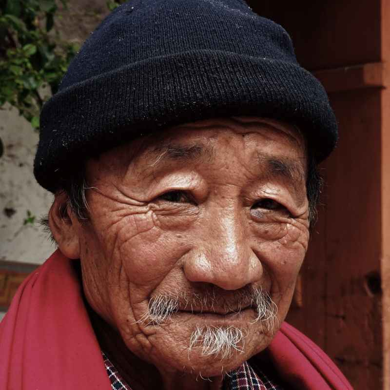 smiling man wearing red scarf and black beanie